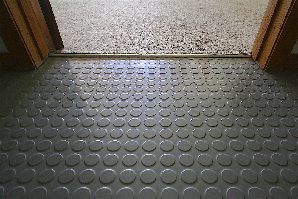 Solid rubber  Mondo®  flooring in the front entrance vestibule (opening into the living room).