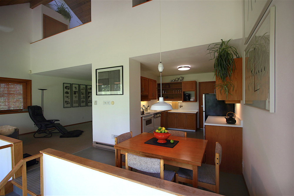 View from the south-east corner, showing the dining area, kitchen, and living area of the main level. On the upper level, the  sleepspace  is on the left and the studio/library is on the right...