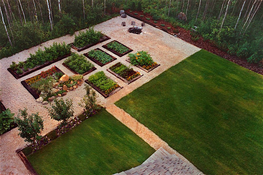 "View down from the ""Eagle's Nest"" to the raised garden beds, rock garden, sunken fire-pit, apple trees, and ""postage-stamp lawn"" — as developed in the 1980s.  Landscaping fabric topped with pea gravel (aka ""buckshot"") was installed on all pathways for ease of maintenance."