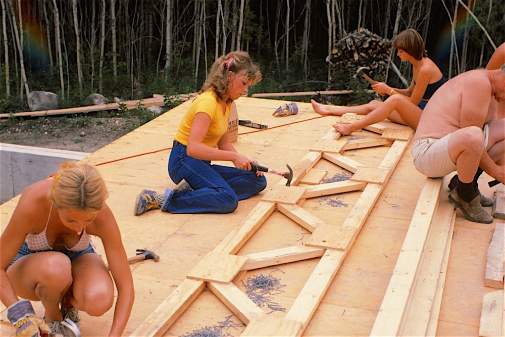 Bevery Pauls along with family members work on the 39 hand-built web trusses (constructed  in-situ by means of custom jigs using the main floor as a platform)... spring, 1980.