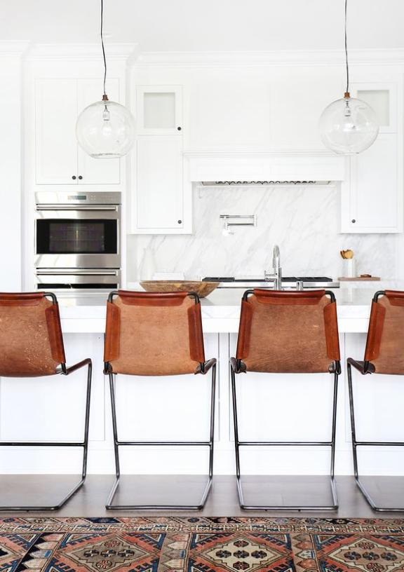 "Love the starkness of this all white kitchen! The leather bar stools and vintage Kilim runner give what could be considered a ""plain"" space an eclectic, collected vibe. I totally want to live here. (source)"