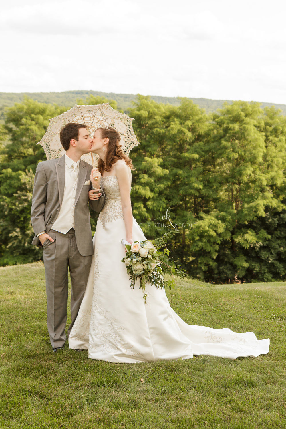 Bride and groom kissing under parasol | Christina Keddie Photography | Finger Lakes NY wedding photographer