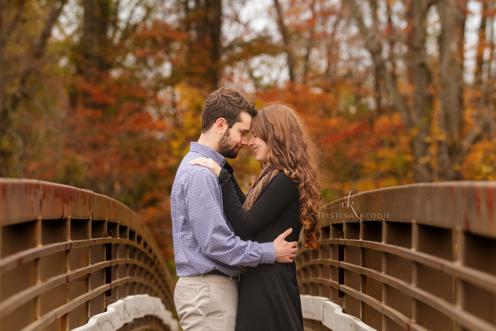 Engaged couple embracing on bridge surrounded by autumn leaves | Christina Keddie Photography | Ewing NJ engagement photographer