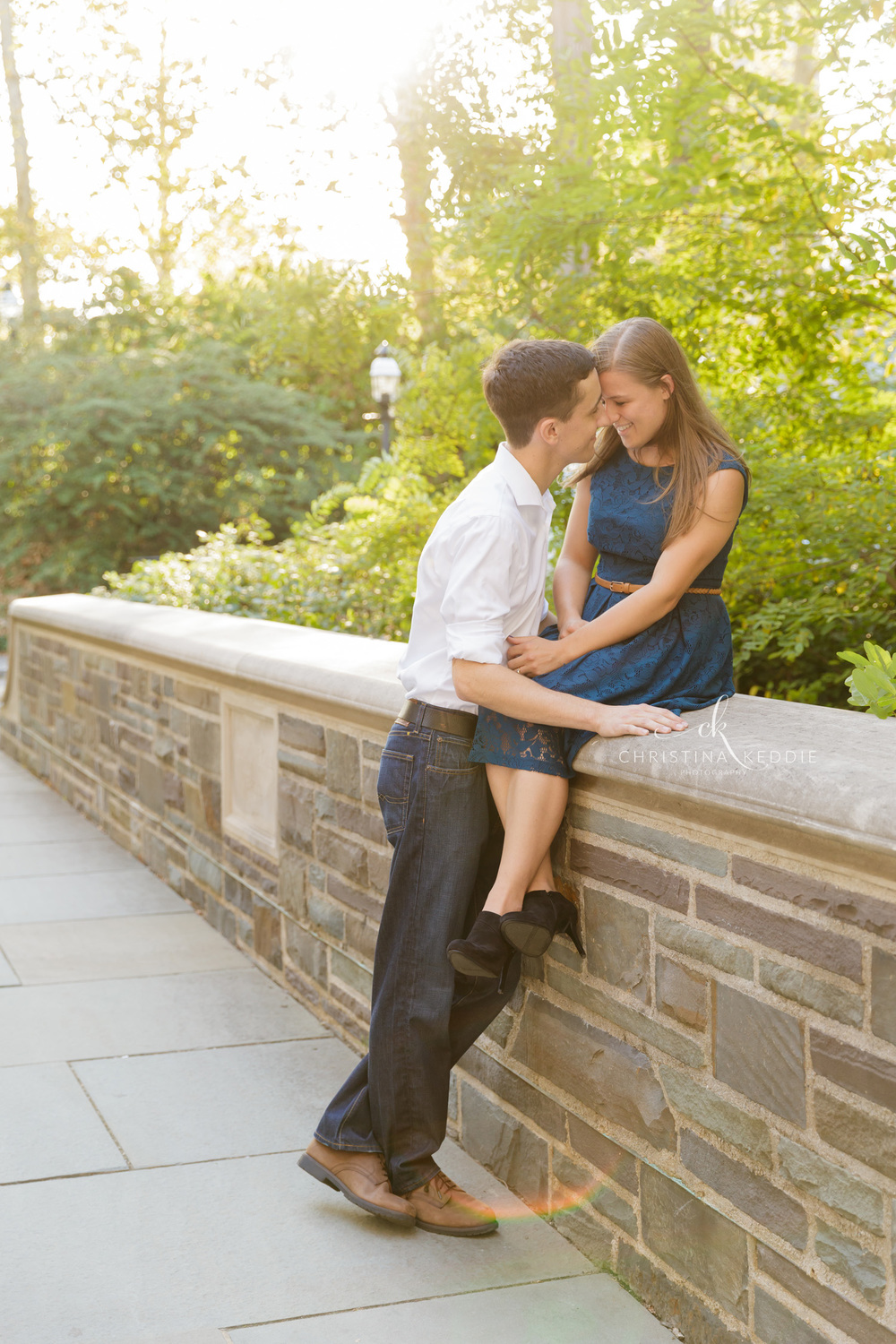 Engaged couple embracing on stone wall | Christina Keddie Photography | Princeton NJ engagement photographer