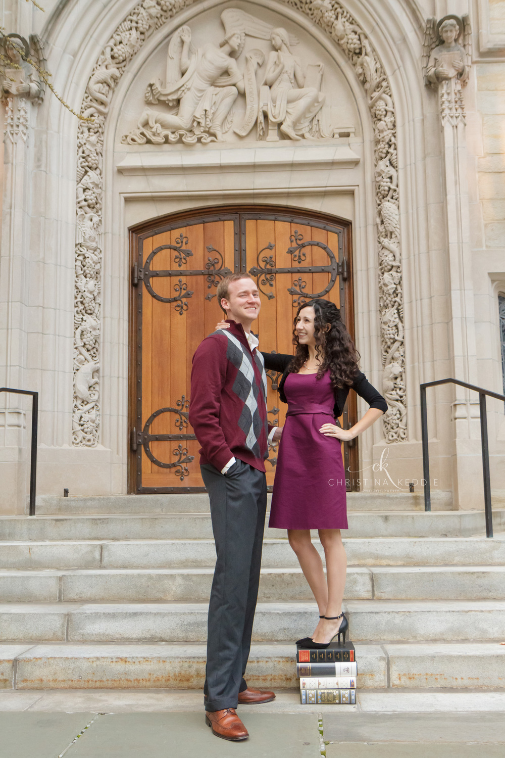 Engaged couple with short fiancee standing on books | Christina Keddie Photography | Princeton NJ engagement photographer