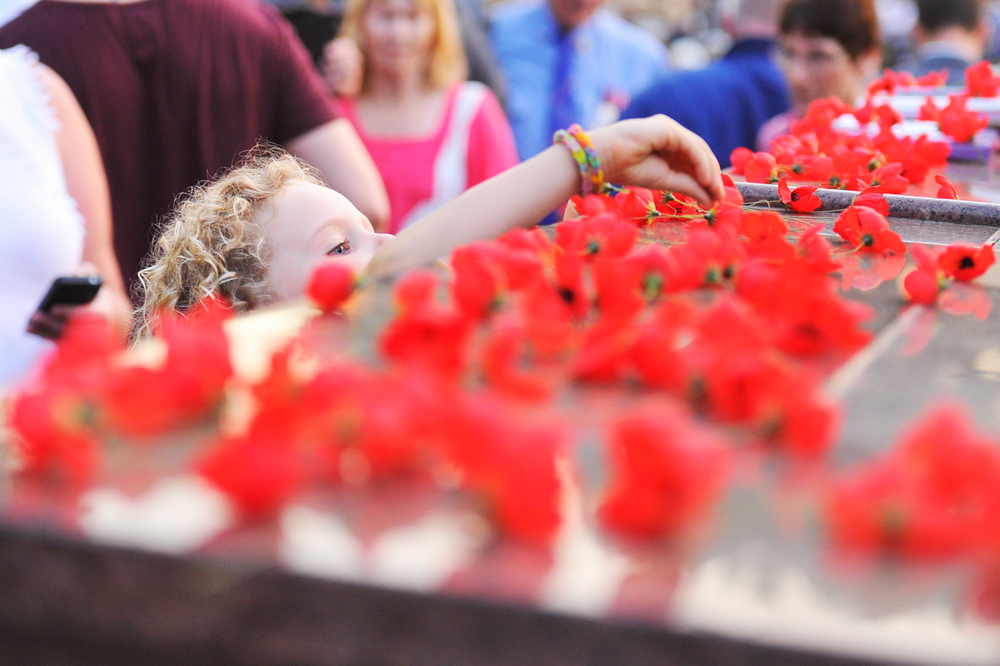 CHP_Export_67519939_A little girls stretches to lay a poppy on the cenotaph at the ANZAC Day Daw.jpg