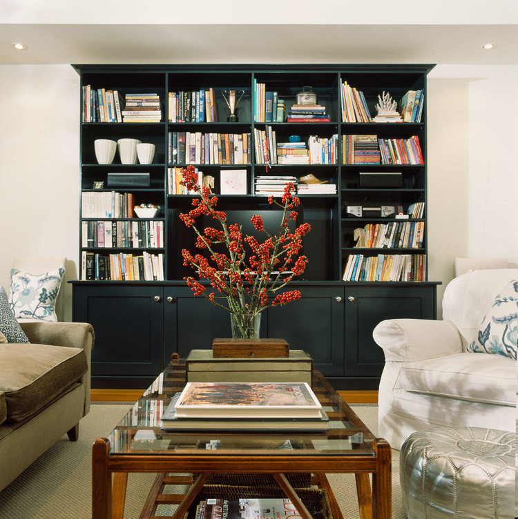 Here books and treasured possessions really pop against the black lacquered bookcase. By Diane Bergeron Interiors.
