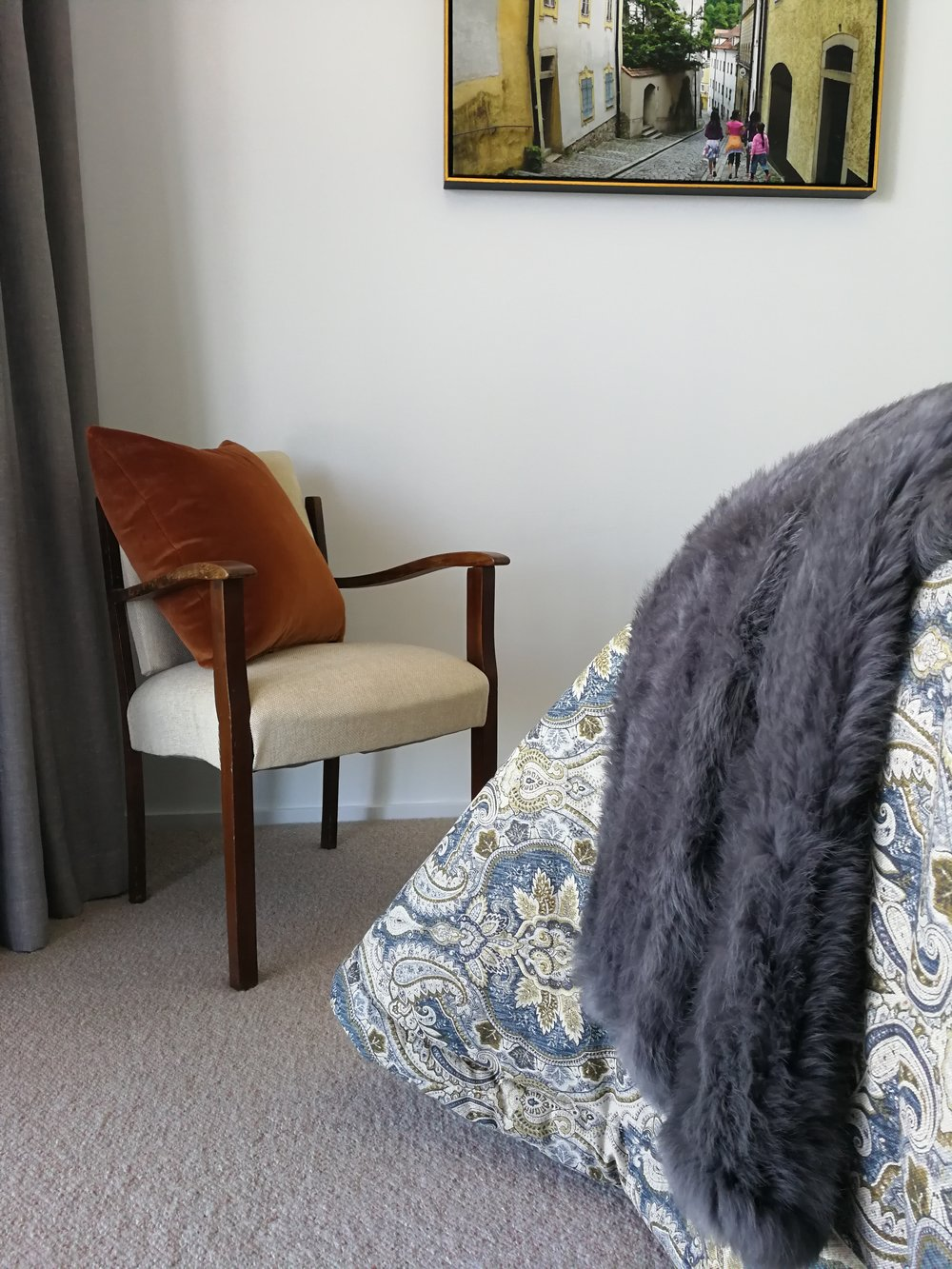 French linen bedspread with rabbit fur throw sits well with a vintage reclining chair.