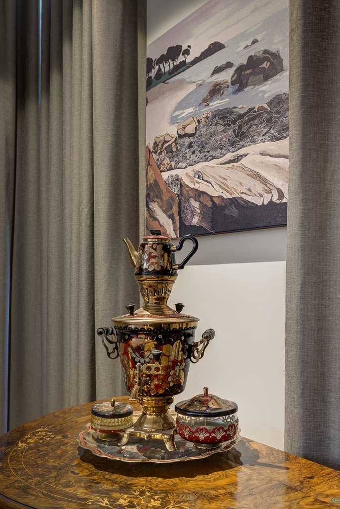 A Ukranian Samovar sits beneath a painting of Eagle Bay, Margaret River