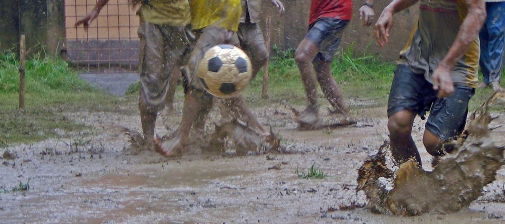 kids playing football in the rain