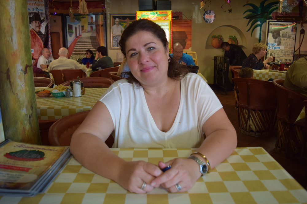 "Laura Gutierrez Ramos   Manager, Nuevo   León   ""This restaurant was opened in 1977.  My father Emeterio Gutierrez, who is the owner, he immigrated when he was 12 years old to Chicago.  My grandfather worked in refineries.  There were four boys.  They did their schooling here not knowing a drop of English, and it was a different school system than it is now.  They went through a lot of hardships, but in the end everything paid out.  Grandmother used to work the soup kitchen at Old St. Pat's school to pay for their education.  She got them to the Catholic grammar school and high school at Holy Name Cathedral.  She used to work the kitchen there too.  Grandma wanted to open up a restaurant.  They opened up the restaurant in Pilsen in 1962, which was a staple in Pilsen that burnt down.  They all started there with their parents, and my father decided to move in 1977 to this location here.  He opened it up with a lot of dreams in every way.  It's pretty hard to do as a Mexican immigrant.  It was a very Bohemian/Czech neighborhood at the time here.  Little Village was nothing what it is now.  He's been open ever since then.  He's had his hardships, but he's made it for 39 years so far.  Now this has been a staple in this community because Little Village has transformed into a Latino, Hispanic community.  Mexicans, Salvadorenos, it's very diverse…Everything is made here fresh.  The food is made with a lot of TLC, a lot of grandma's recipes…fresh homemade tomales, tortillas de harina, which are from the northern part of Mexico where my father is from.  We take a lot of time and inspiration in our food…We're actually a pretty tight-knit community.  Little Village has a lot of ups and downs of course.  And I know the feedback from TV, the negligence on the gangbangers, the gangs, this and that, it's not all about that.  There's still a lot of heart in this community.  And at the end of the day we all come together."""