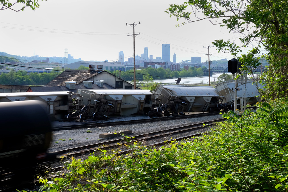 An oil car speeds past a derailed train in the Hazelwood neighborhood of Pittsburgh.  Downtown Pittsburgh is less than three miles away.  © Brian Cohen, 2015.