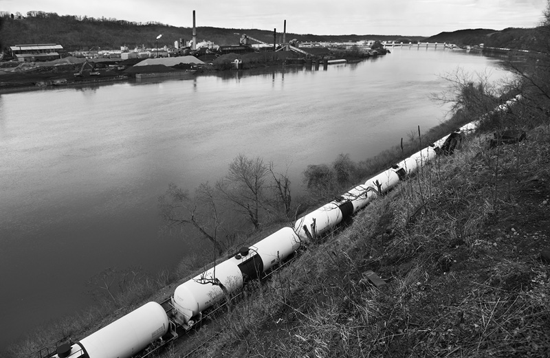 "A train loaded with crude oil rolls past the Shenango Inc. coke works near Pittsburgh, PA. The U.S. Environmental Protection Agency describes coke oven emissions as ""among the most toxic of all air pollutants."" The train is carrying crude oil from the Bakkan oil field in North Dakota. These trains have derailed numerous times across the U.S. causing extreme air and water pollution. The oil they carry will be burned for energy, causing further release of fine particulates. The trains themselves become air polluters along the route.  © Scott Goldsmith/TDW 2015"
