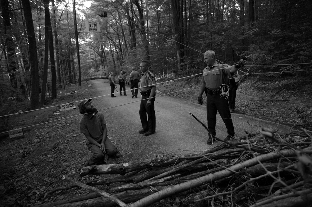 One of many activists who shut down a large drilling operation in Moshannon State Forest sits behind a barricade of brush, locked to a rope. The activists held off police efforts to open the road to the rig, which forced its shutdown for an entire day.  ©   Lynn Johnson/MSDP 2012