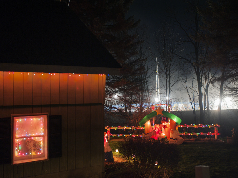 Bright lights illuminate a Hallburton fracking site situated next to the leaseholder's home which is decorated with Christmas lights. Franklin Forks, Susquehanna County, 2011.  ©   Nina Berman/MSDP 2011
