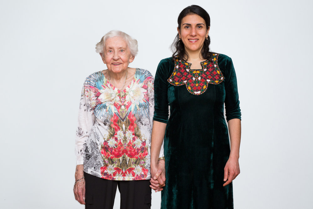 "Gertrud Wunder was born in East Prussia, Germany. She arrived in the U.S. in 1952.     Meryembibi Mammedova was born in Turkmenistan. She arrived in the U.S. in 2005.     Both come from countries that are part of the former U.S.S.R.     Gertrud moved to the U.S. with her husband and five-year-old daughter for more opportunities. There was not a lot of work in war-torn Germany where they were living. They were sponsored by relatives living in New York City.     Meryembibi met her husband while he was serving in the Peace Corps in Turkmenistan. Soon after they were married, they moved to the U.S.     Gertrud: ""My aunt and uncle picked us up from the boat. The next morning, we went out for a walk around the neighborhood and I have to mention this. I saw in the garbage cans these big loaves of bread, not even used, not open, nothing. And we had hunger big you know, we were starving over there at times. When we came home, I said to my aunt, 'What is this, all those loaves of bread in the garbage can?' 'Yes, they only eat very fresh bread. This is too old. That's why they put it in a garbage can.' I never could get over that.""     Meryembibi: ""The first year was rough because I came here from a country where it's all about family and we gather a lot. I didn't spend a day without the family. And when I came here I only had my husband and then my parents-in-law. But they live in a different neighborhood and we would see them but it wasn't something I was used to. So, for me it was a shock.""       Annie O'Neill/TDW 2017"