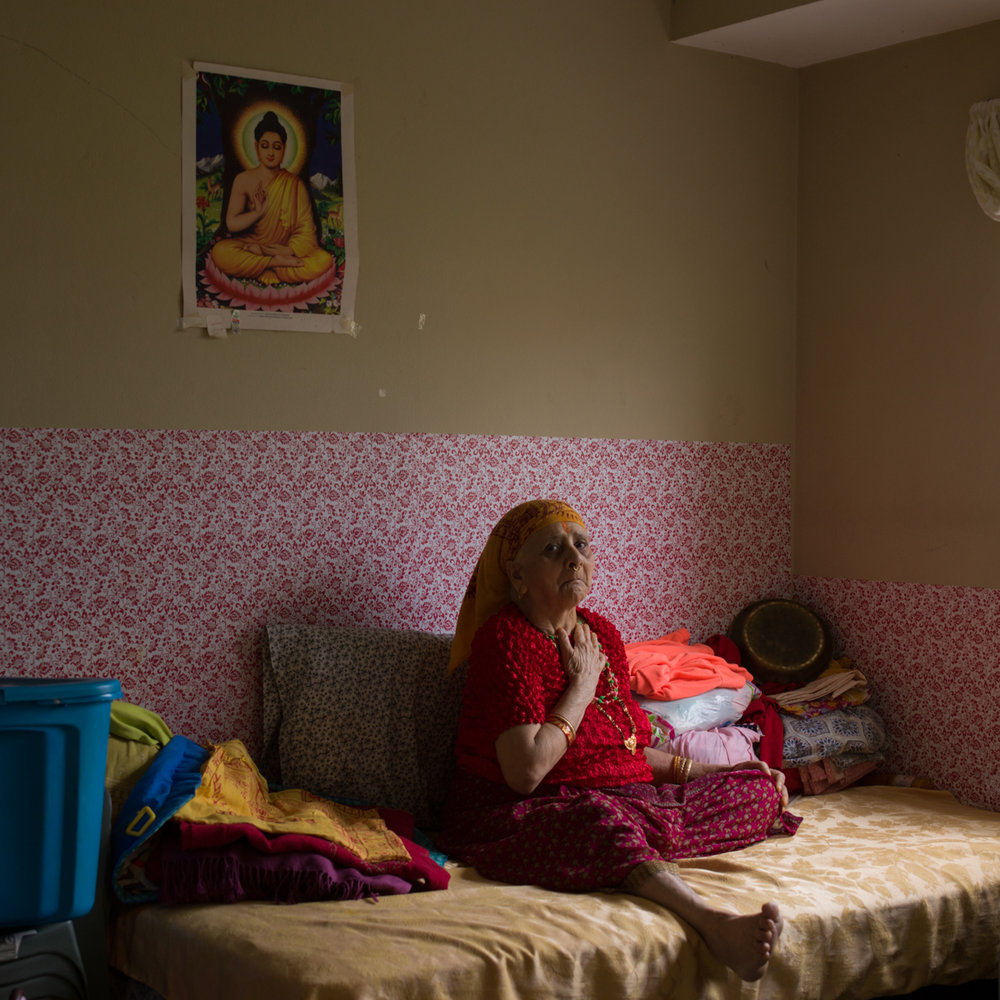 Sabitra Subedi is Bhutanese from Nepal. Her room in this modest apartment in Pittsburgh, home for the past six years, is part shrine and part storage for the multiple generations that live here.  © Lynn Johnson/TDW 2017