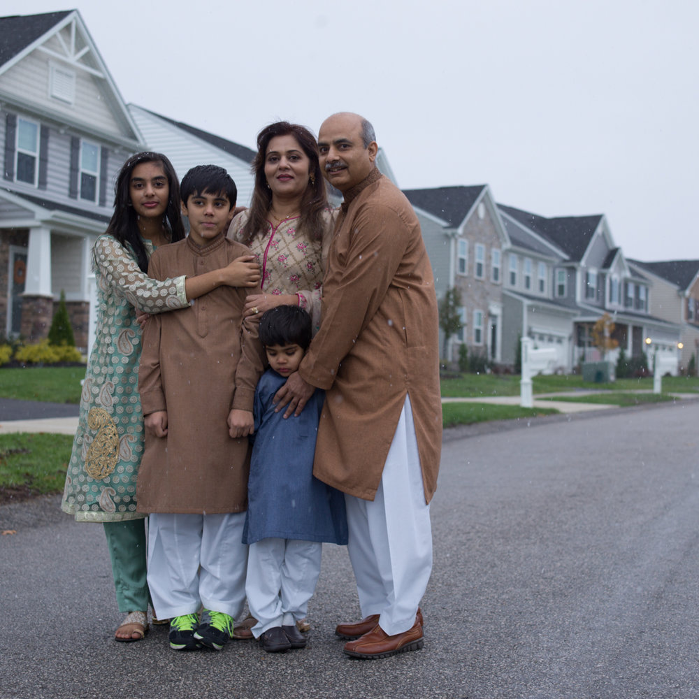 Mirza family from Pakistan: Naeem Mirza, fifty-one; Raqna Mirza, forty-two; Laiba Mirza, fourteen; Mohid Mirza, twelve; Muhab Mirza, four.     Naeem Mirza has been in the U.S. for eighteen years. His first visit was in 1999. His company transferred him permanently in 2001. The Mirza children dress in American attire except when they must don traditional clothes for the photograph session. The family, originally from the flat, hot, dry part of Pakistan, stand outside in the first snow of the season in their suburban neighborhood.  © Lynn Johnson/TDW 2017