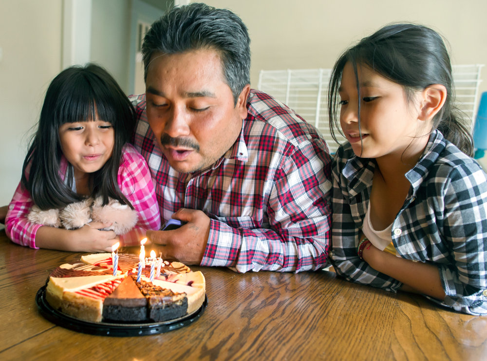 Brianna and Emma look on as Jose blows out candles on a birthday cheesecake. He was celebrating with his daughters and a few friends.  © Nate Guidry/TDW 2017