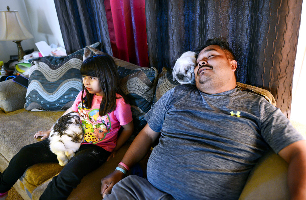 Briana and Jose with their pet rabbits, while watching television.  © Nate Guidry/TDW 2017