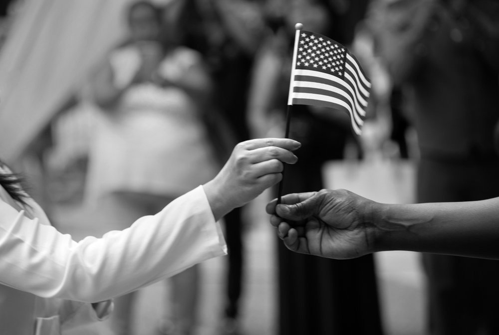 Refugee Day, Market Square, Pittsburgh, Wednesday, June 21, 2017. One of eleven new U.S. citizens is given an American flag during a naturalization ceremony in downtown Pittsburgh. After she was given the flag, she received her certificate of citizenship. The event took place in Market Square amid the aroma of foods from myriad countries.  © Scott Goldsmith/TDW 2017