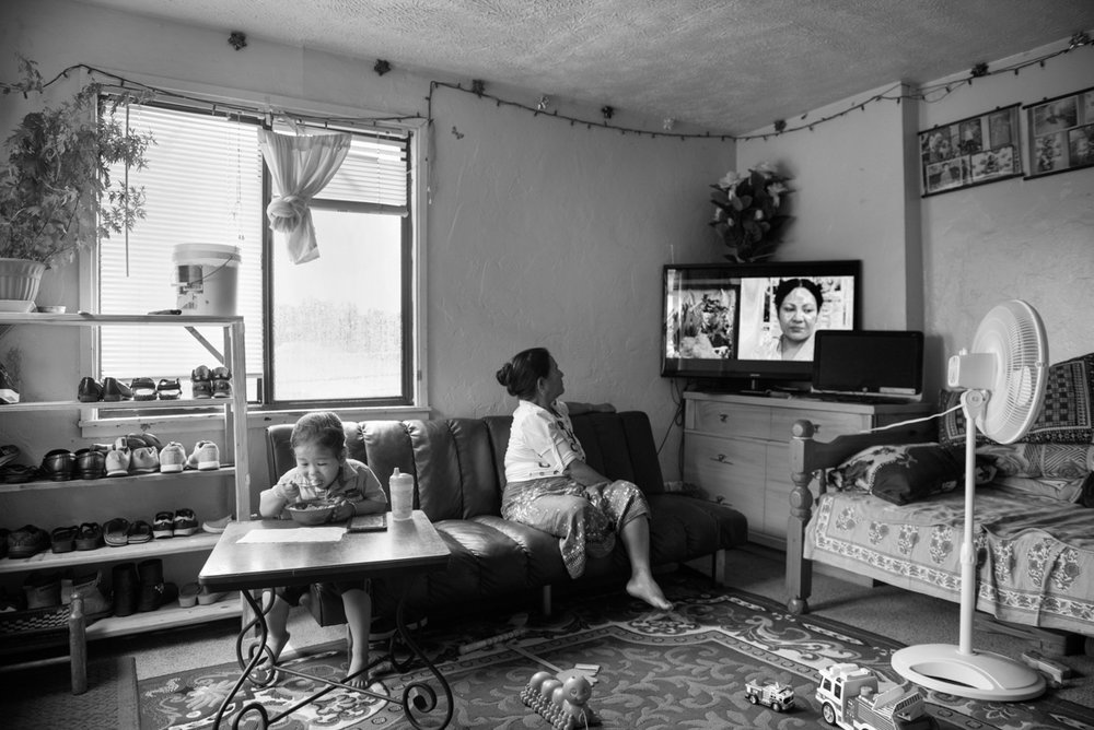 The young boy on the left is the grandson of the lady on the right. The lady on the right immigrated to the US this year with her daughter and son-in-law. She is mesmerized by TV. She had never watched TV until she came to the USA. They have direct TV and watches a channel broadcast from Nepal almost non stop during her waking hours.  © Scott Goldsmith/TDW 2017