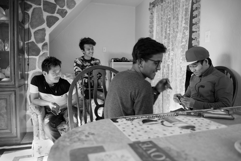 Som has developed a small group of friends in his neighborhood that is comprised of 80% refugees from 6 different countries. These boys are meeting at Som's apartment shortly before Som departed for work. They are working together to replace a Sim card in an old cell phone.  © Scott Goldsmith/TDW 2017