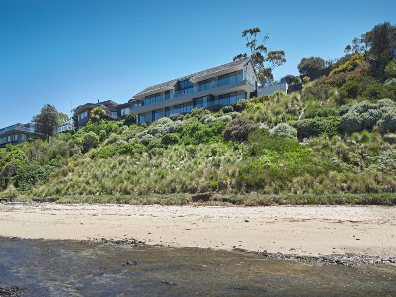 Architect-designed four bedroom, 5.5 bathroom plus a study residence with actual beach frontage has been crafted into the cliff face in Flinders most prestigious waterfront cul-de-sac