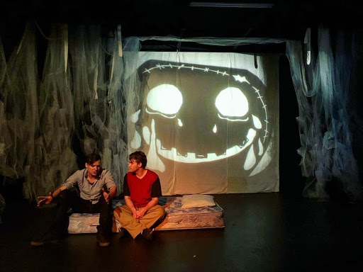 Aaron Dismuke (left) and Robert Linder (right) act in front of shadow puppets.