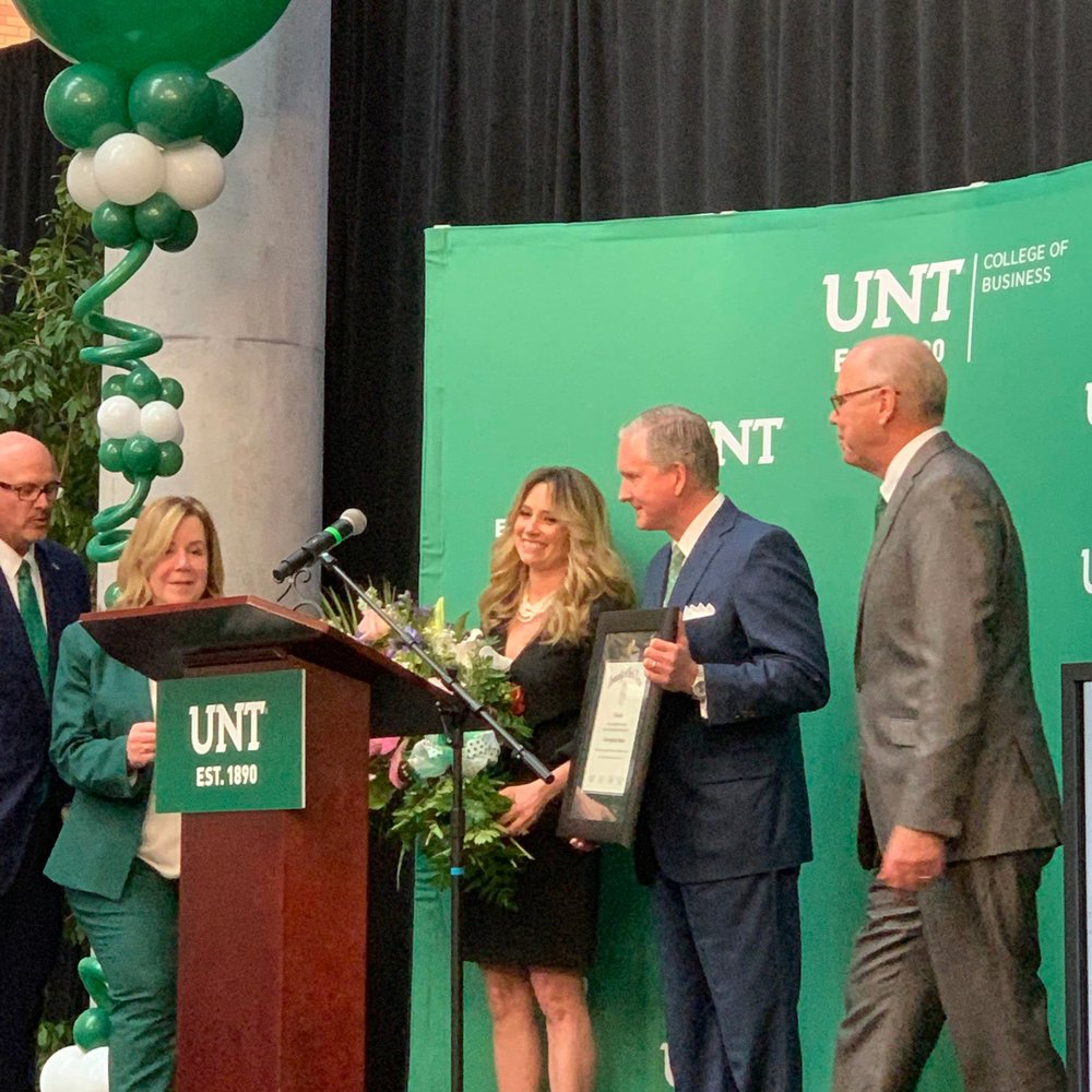 Standing ovation as President Smatresk hands the donors - Brint and Amanda Ryan - flowers and a plaque in thanks for their donation to the UNT College of Business.