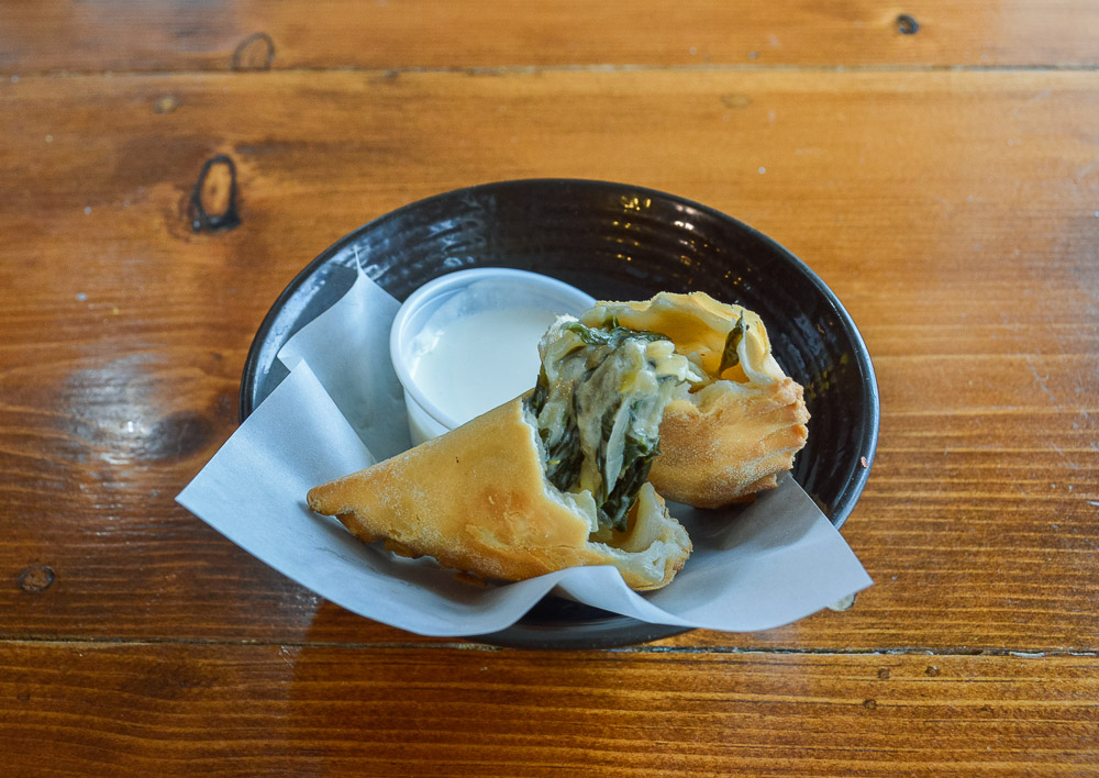 Spinach, goat cheese & caramelized onion empanada with garlic crema.
