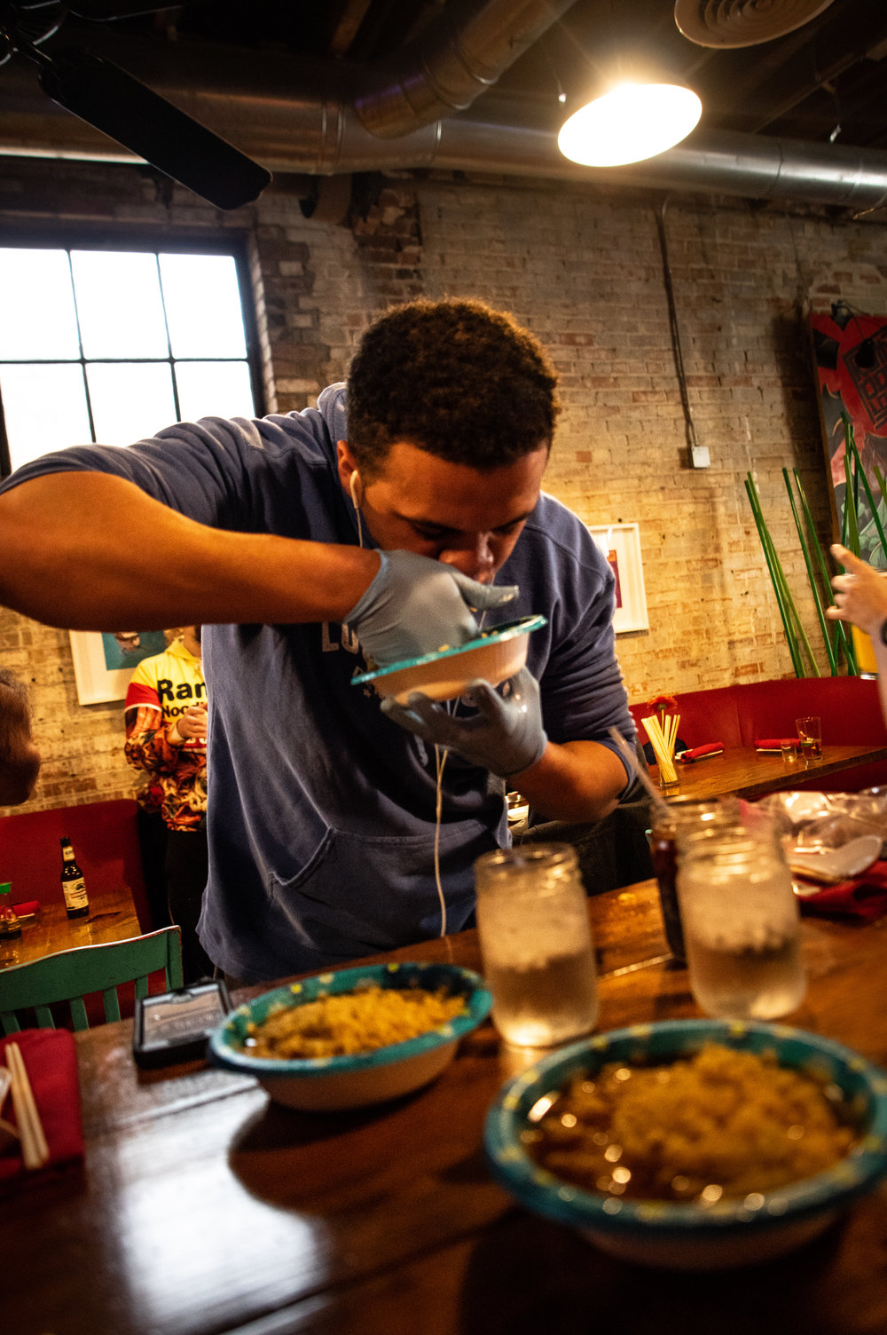 Alaric Ukeh, representing Lucky Lou's, dons medical gloves and earbuds as he digs in for the ramen eating competition.