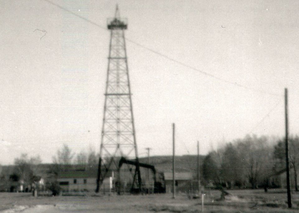 Here is a (regrettably blurry) view from the same angle as the previous slide. This type of rig -- derrick, pump, tin engine house -- was repeated dozens and dozens of times throughout the field in the early days; Not all wells had derricks, but those drilled by Stanolind (later Pan American Oil) did -- and there were many of them.