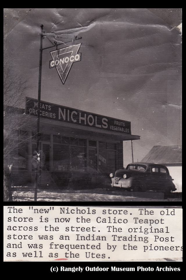 "Another view of the ""new"" Nichols store, perhaps taken about the same time as the previous one (is that the same sedan sitting out front?) The gas pumps are either just off-screen to the right, or (perhaps) have been removed by this time...  The caption claims the old store across the street had now become a business called the ""Calico Teapot""."