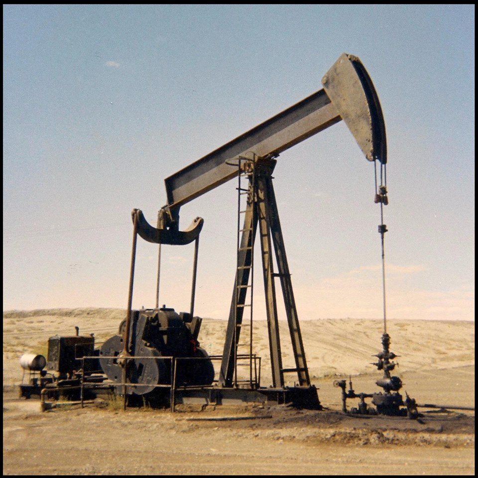 """1) ANCIENT LUFKIN. From its perch on the very top center of the Rangely Anticline, the A-1 well flowed by itself at first.  By 1971, however (when young Oil Geek took this photograph with a Kodak Instamatic (TM) 126 camera), the well had been """"on the pump"""" for quite a long time, as evidenced by this early Lufkin model 64 conventional oil pump."""