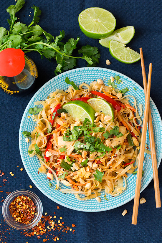Chicken Pad Thai Yield: About 5 servings Ingredients 10 oz Thai rice noodles 1 lb boneless skinless chicken breasts, sliced into small strips 2 Tbsp vegetable oil 1/4 cup packed dark-brown sugar 1/4 cup soy sauce 2 Tbsp rice vinegar 1 Tbsp lime juice 1 Tbsp fish sauce 1 red bell pepper, sliced into thin strips and strips halved 1 1/2 cups matchstick carrots 2 cloves garlic 4 green onions, whites minced, greens sliced into 1-inch pieces 2 cups bean sprouts 3 large eggs 1/2 cup unsalted peanuts, roughly chopped 1/3 cup cilantro, chopped Red pepper flakes and sesame seeds (optional) Directions Prepare rice noodles according to directions listed on package. In a mixing bowl, whisk together brown sugar, soy sauce, rice vinegar, lime juice and fish sauce, set aside.  While noodles are cooking, heat oil in a wok or large and deep non-stick skillet over medium-high heat. Once hot add chicken and saute until cooked through, about 4 - 6 minutes. Transfer to a plate, leaving oil in pan. Add bell pepper and carrots and saute 1 - 2 minutes then add garlic, green onions and bean sprouts saute 1 minute longer. Push veggies to edges of pan and crack eggs into center. Cook and scramble until eggs have cooked through. Add in chicken, noodles and sauce and toss everything together and cook 1 - 2 minutes.  Serve warm topped with cilantro, peanuts and optional red pepper flakes and sesame seeds. Recipe source: Cooking Classy