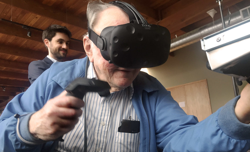 Jake Rubin shares AxonVR's HaptX demo with his grandfather.