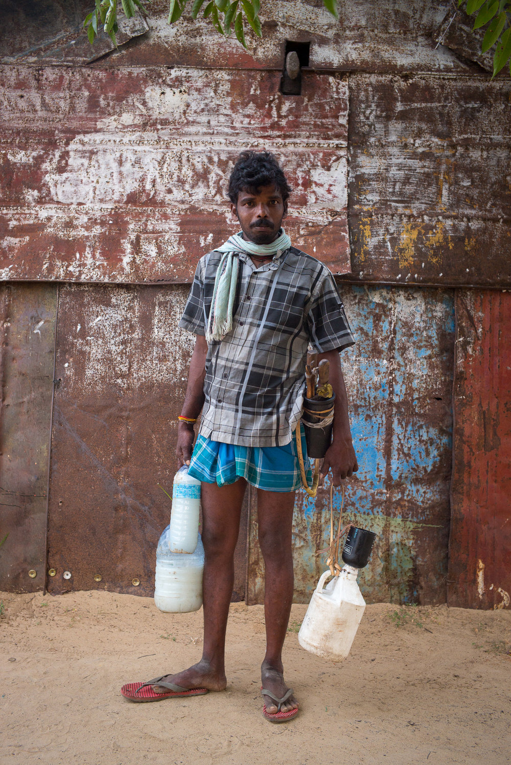 A tapper brings the afternoon's toddy to the cooperative at Pothikkadu.