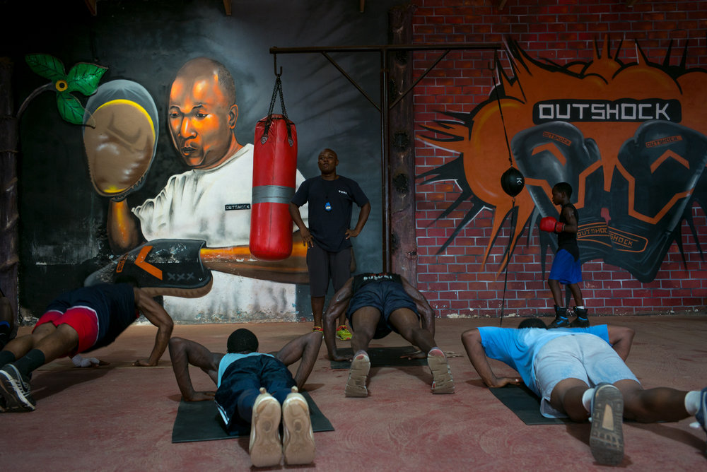 Coach Rossy, 36, training his boxers. On the wall: Portrait of Coach Adama, founder of The Gym, Ussher Town.