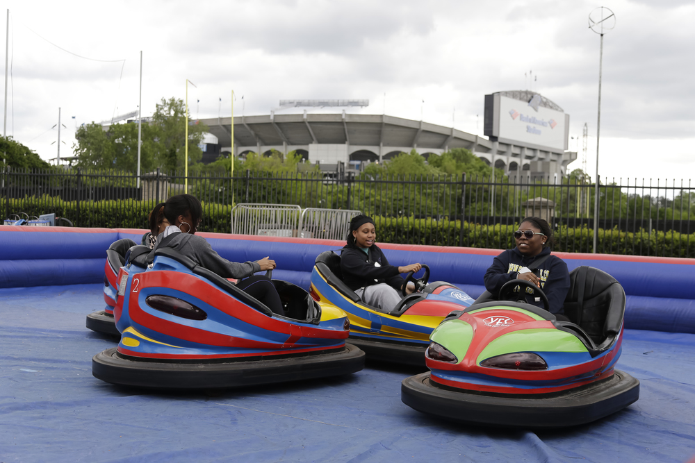 Students ride bumper cars at a JWU event