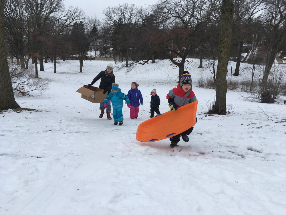 We play outside as much as possible. Here we discovered that cardboard boxes work amazingly well as a sled.