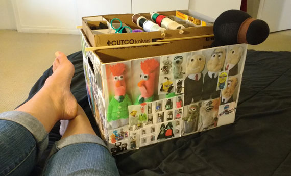 """This is a file box that I covered with photos of past creations and use to carry the bigger items like stuffing, and 5-10 sock animal bodies that I'm working on. That's a bear for Jasper """"Bear's Paw Bakery"""" peeking out of the box."""