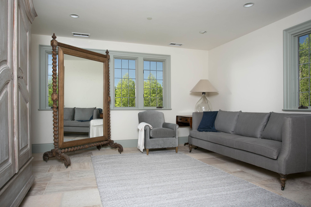 An antique French cheval mirror is the centerpiece in the living area of the guest house