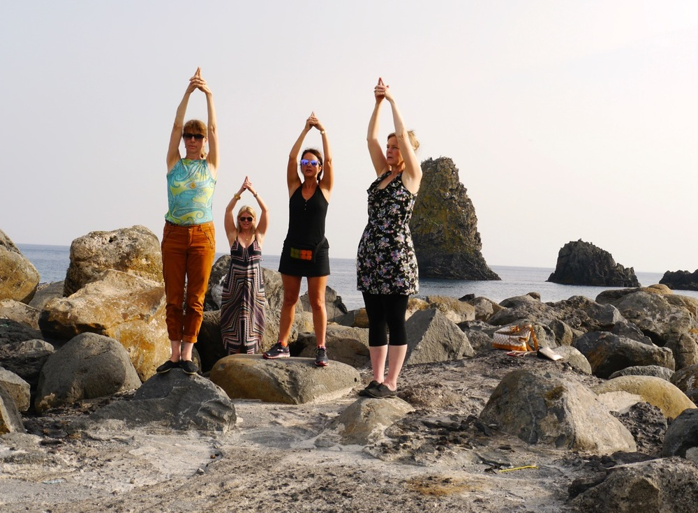 Practicing Kundalini yoga exercise at the seaside in Sicily, Italy (co-led retreat with La RosaWorks).