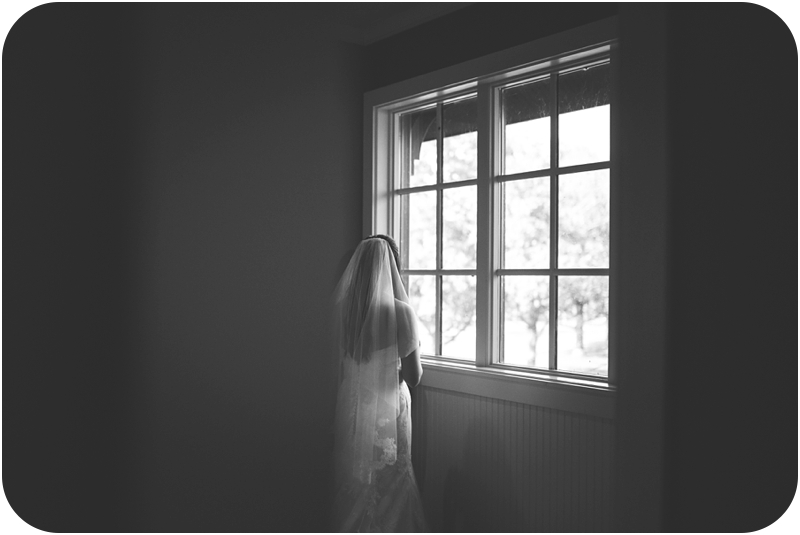 black and white photo of bride looking out window at fasig tipton lexington farm wedding