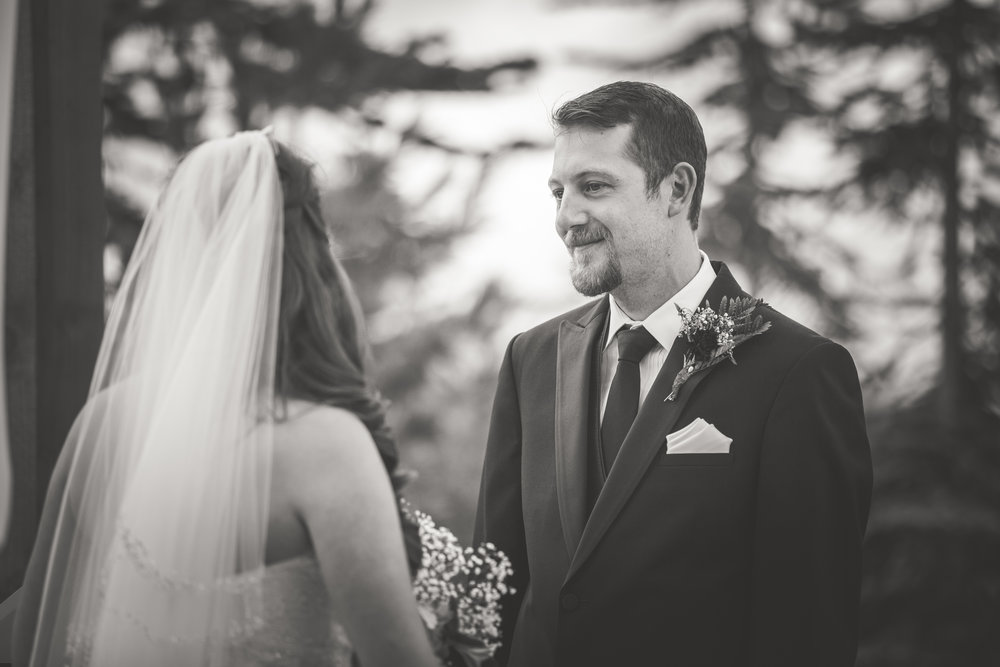 black and white image of groom looking at bride