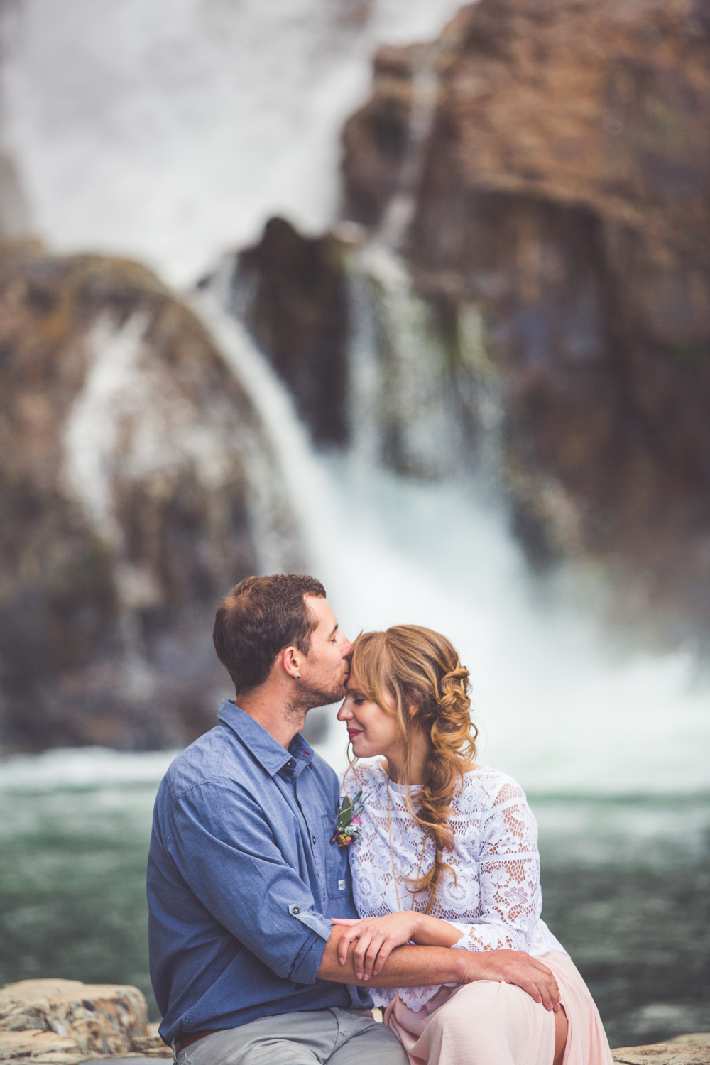 groom kisses bride at myra falls in strathcona park
