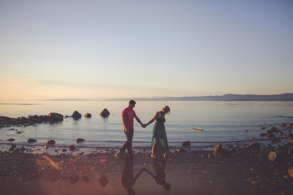 couple walks on beach at sunset in Qualicum Beach