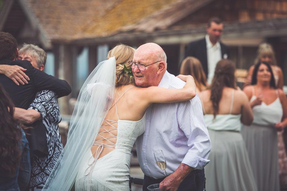 bride hugs her grandfather after Qualicum Beach wedding ceremony