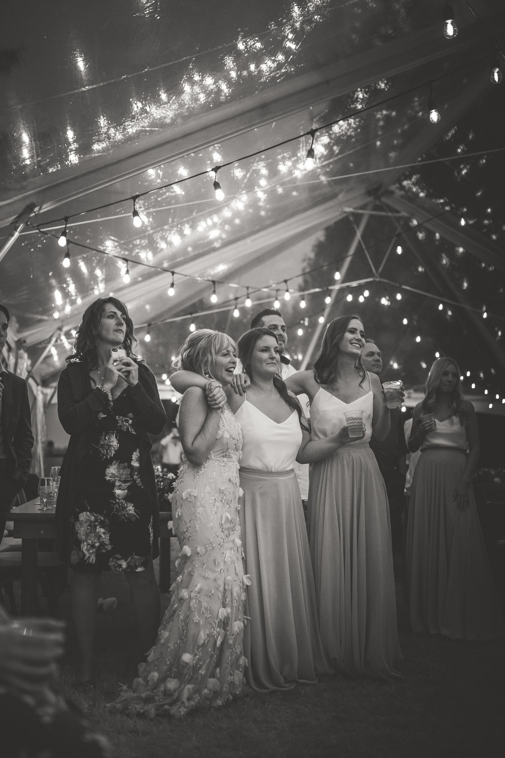 family joyfully watches bride and groom first dance under twinkle lights in Qualicum Beach
